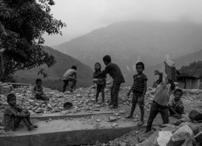 Children from Simjung VDC, Gorkha , help eacher to pile up the stone from debris of a house.